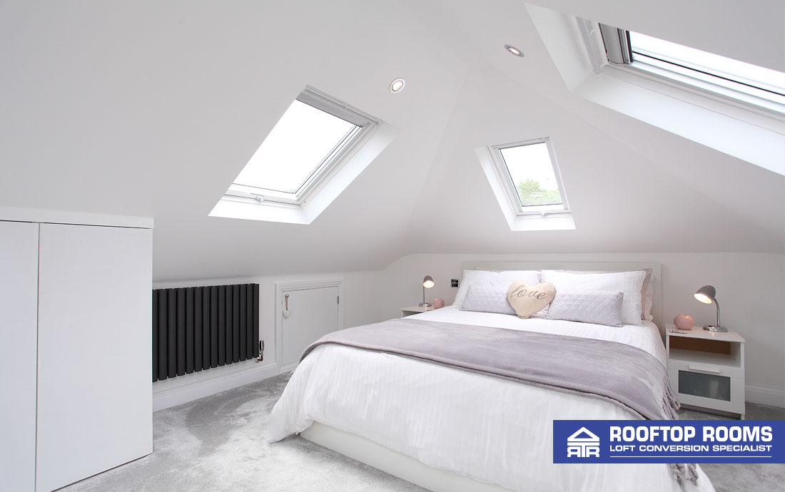 Velux loft conversion bedroom with windows on three sides.